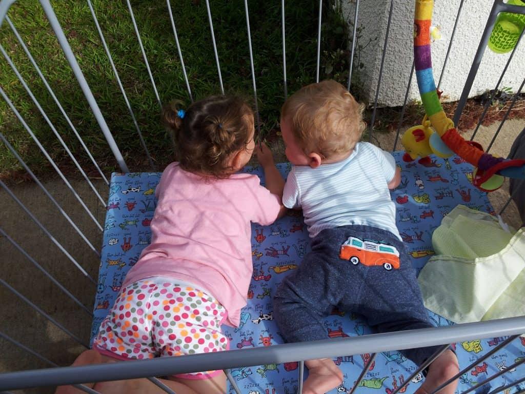 שני ילדים שוכבים בעגלול לתינוקות